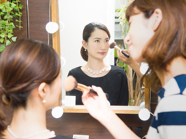 プロフィール写真の撮影のためにヘアメイクを受けるビジネスマンの写真